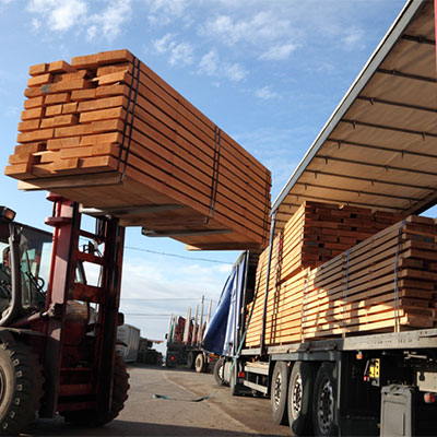 mini forklift carrying stacks of wood panels