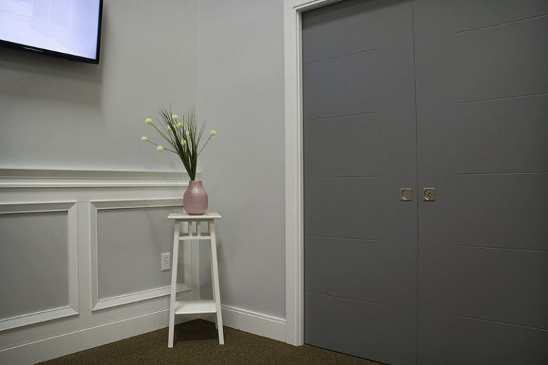 gray door and plant in a vase sitting on top of a white stool
