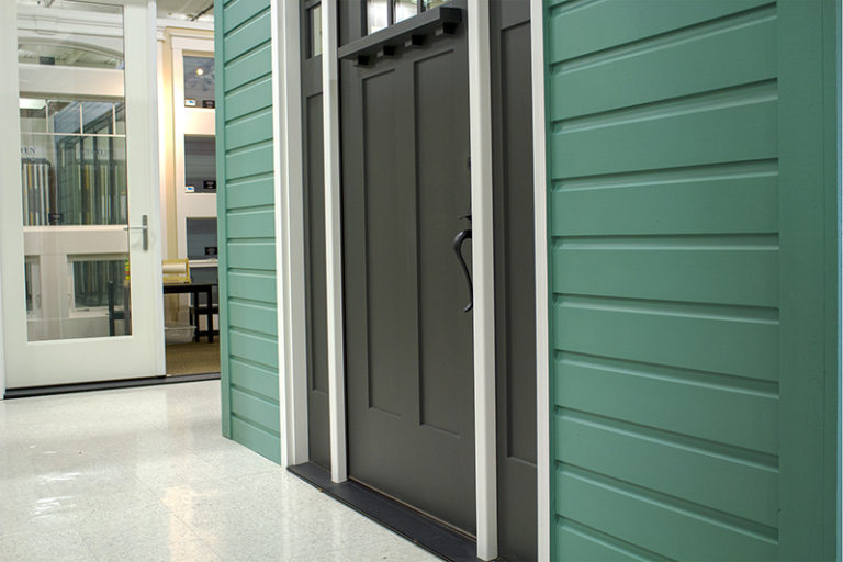 gray door on a green siding house
