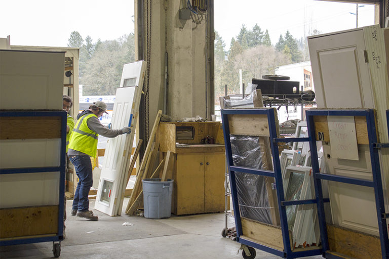 Builders FirstSource Oregon workers carrying doors